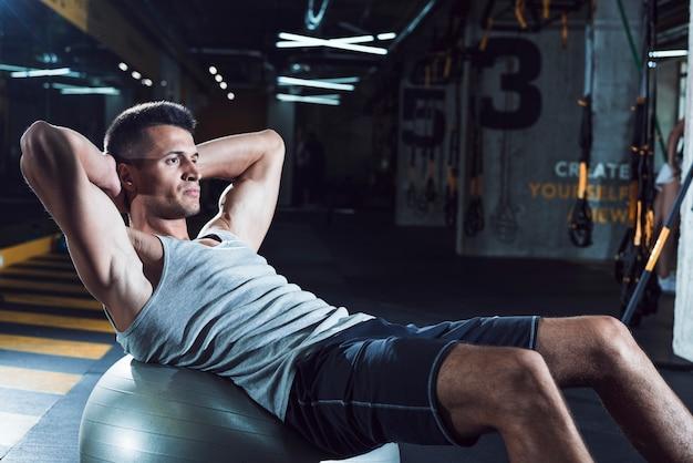 Vista lateral, de, um, homem jovem, exercitar, ligado, esfera aptidão Foto gratuita