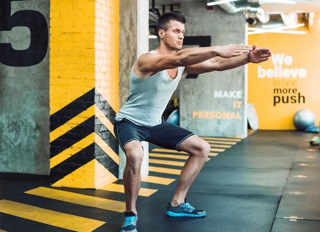 Vista lateral, de, um, homem jovem, fazendo, exercício, em, clube aptidão Foto gratuita