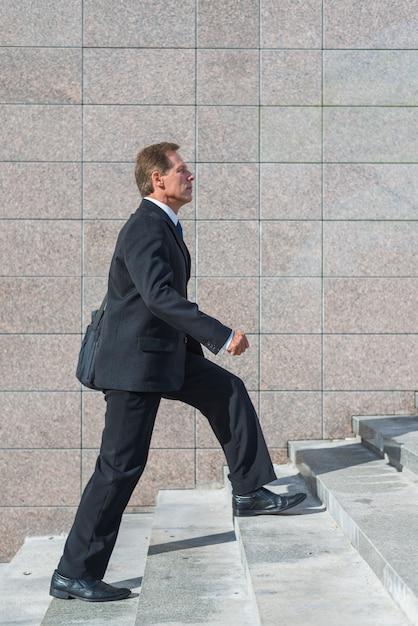 Vista lateral, de, um, homem negócios maduro, escalando, escadaria Foto gratuita