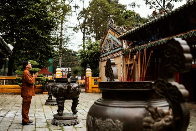 Vista lateral de um homem orando no templo com incenso Foto gratuita