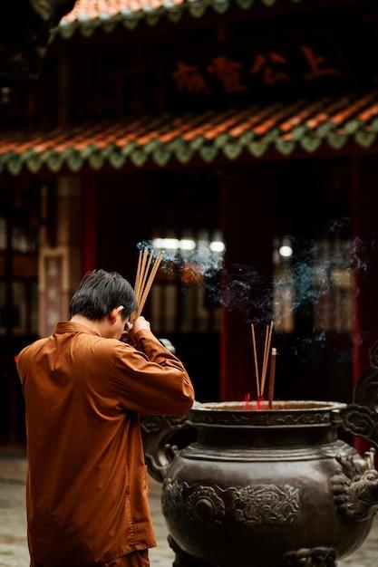 Vista lateral de um homem religioso no templo queimando incenso e copiando espaço Foto gratuita