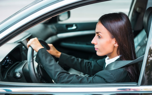Vista lateral, de, um, jovem, executiva, dirigindo carro Foto gratuita