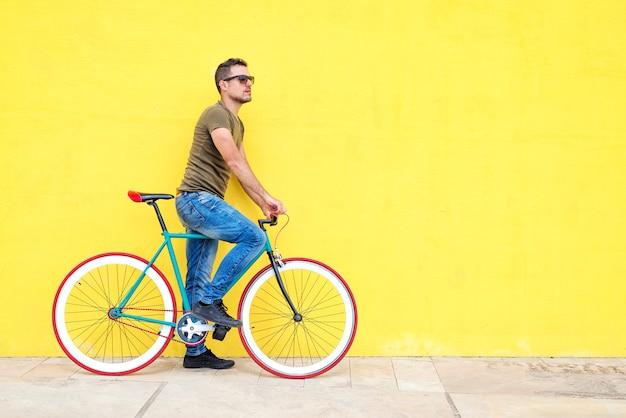 Vista lateral, de, um, jovem, hipster, homem, com, um, fixo, bicicleta, desgastar, roupas casuais Foto Premium