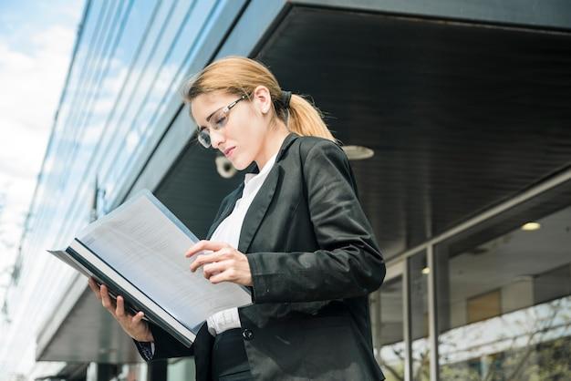 Vista lateral, de, um, jovem, mulher negócios fica, sob, a, incorporado, predios, leitura, a, documento Foto gratuita