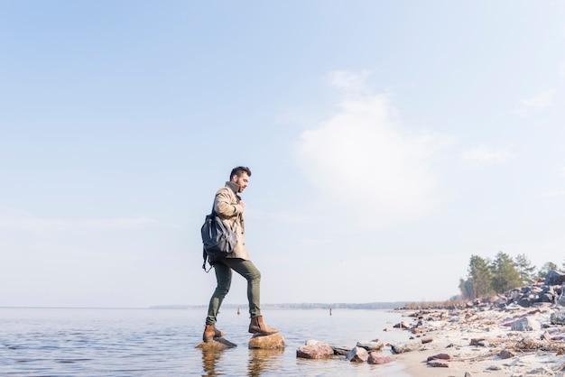 Vista lateral, de, um, macho, viajante, com, seu, mochila, ficar, ligado, a, pedras, em, a, lago Foto gratuita