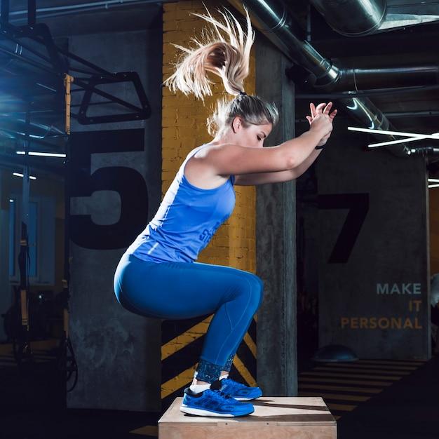 Vista lateral, de, um, mulher, fazendo, malhação, em, ginásio Foto gratuita