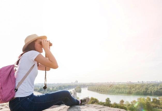 Vista lateral, de, um, mulher olha, vista, através, binóculos Foto gratuita