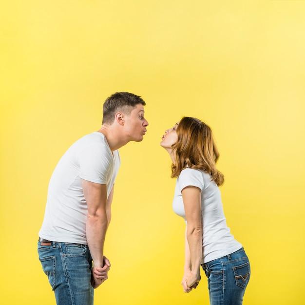 Vista lateral, de, um, par jovem, ficar, cara enfrentar, soprando, beijos, contra, fundo amarelo Foto gratuita