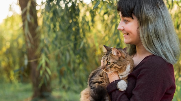 Vista lateral, de, um, tingido, cabelo, mulher, abraçar, dela, gato malhado, em, floresta Foto gratuita