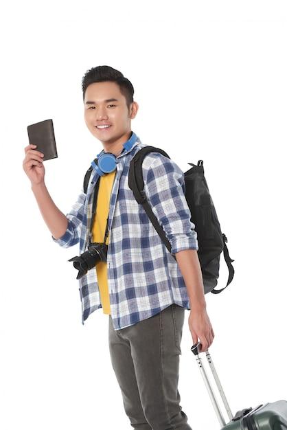 Vista lateral de um turista com bagagem de mão, pronta para apresentar seu passaporte Foto gratuita
