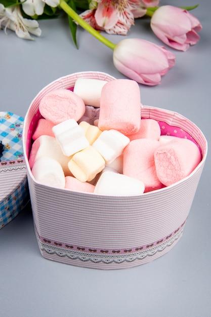 Vista lateral de uma caixa de presente em forma de coração cheia de marshmallow e tulipas cor de rosa com flores de alstroemeria na mesa branca Foto gratuita