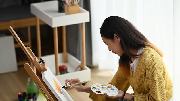 Vista lateral de uma jovem artista com uma paleta na mão desenhando a imagem em seu estúdio. Foto Premium