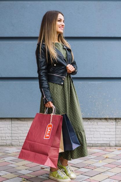 Vista lateral de uma jovem elegante, vestindo jaqueta segurando sacolas de compras na mão Foto gratuita