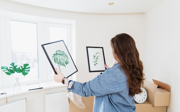 Vista lateral de uma jovem mulher escolhendo moldura para sua nova casa Foto gratuita