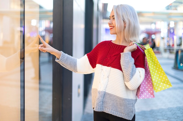 Vista lateral de uma jovem sorridente em pé em um shopping center Foto Premium