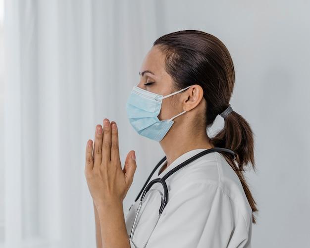 Vista lateral de uma médica com máscara médica rezando Foto gratuita