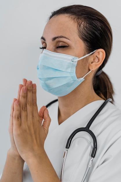 Vista lateral de uma médica rezando Foto gratuita