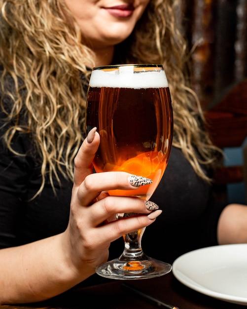 Vista lateral de uma mulher com um copo de cerveja Foto gratuita
