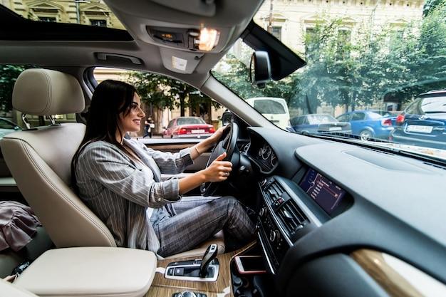 Vista lateral de uma mulher de negócios jovem frustrada, dirigindo um carro. Foto gratuita