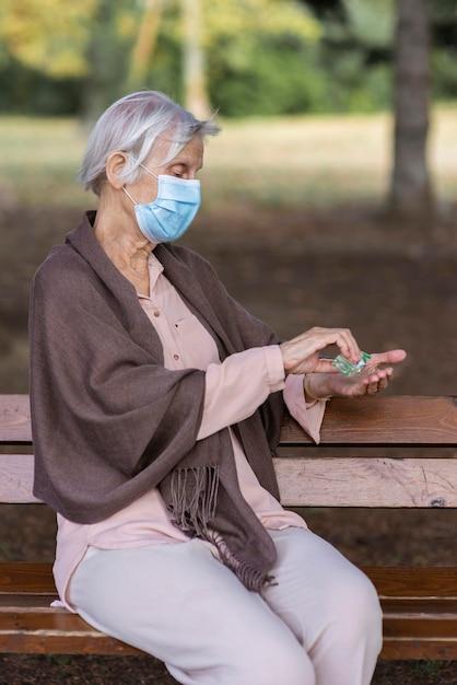 Vista lateral de uma mulher idosa com máscara médica e desinfetante para as mãos Foto gratuita