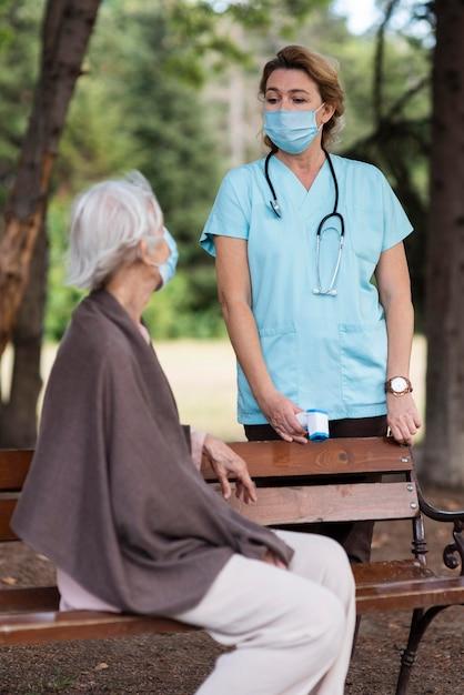 Vista lateral de uma mulher idosa com máscara médica em uma casa de repouso com uma enfermeira Foto gratuita