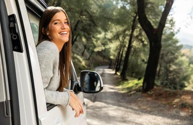 Vista lateral de uma mulher sorridente no carro durante uma viagem Foto gratuita