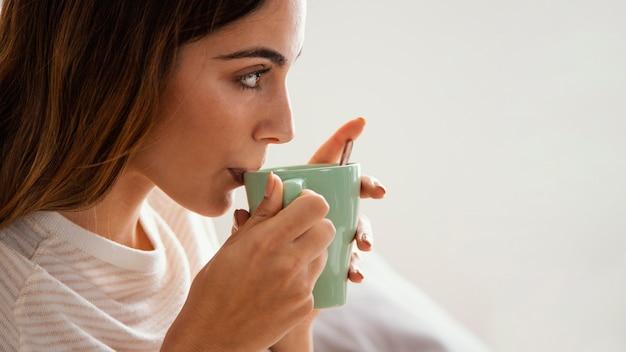Vista lateral de uma mulher tomando café na cama com espaço de cópia Foto gratuita
