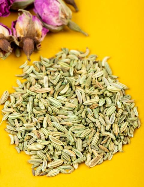 Vista lateral de uma pilha de sementes de anis secas com botões de rosa chá em fundo amarelo Foto gratuita