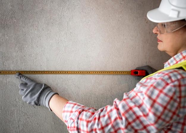 Vista lateral de uma trabalhadora da construção civil com capacete e fita métrica Foto gratuita