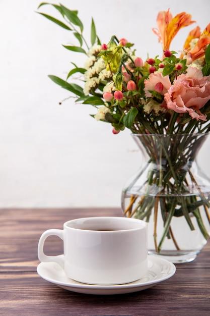Vista lateral de uma xícara de chá com lindas flores em um vaso de vidro em uma mesa de madeira na parede branca Foto gratuita