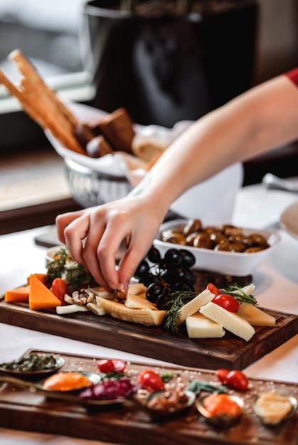 Vista lateral de vários tipos de queijo com uvas nozes e mel na bandeja de madeira Foto gratuita