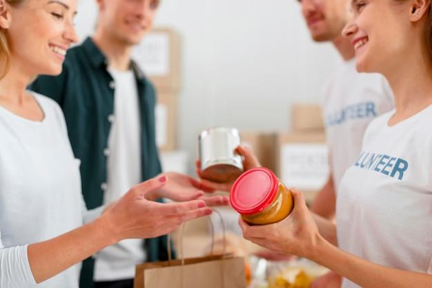 Vista lateral de voluntários alegres distribuindo doações de alimentos Foto gratuita