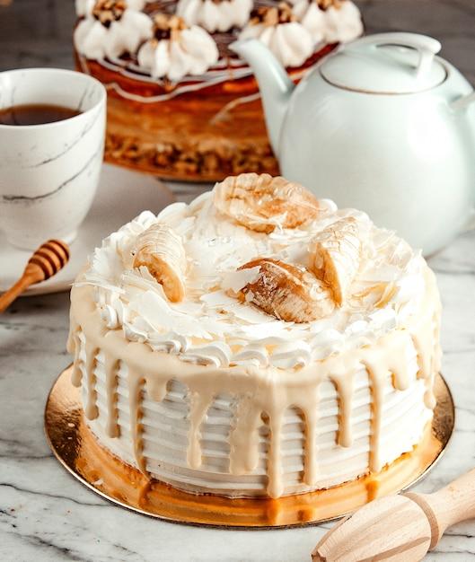 Vista lateral do bolo branco decorado com chantilly de chocolate branco derretido e bananas na mesa Foto gratuita