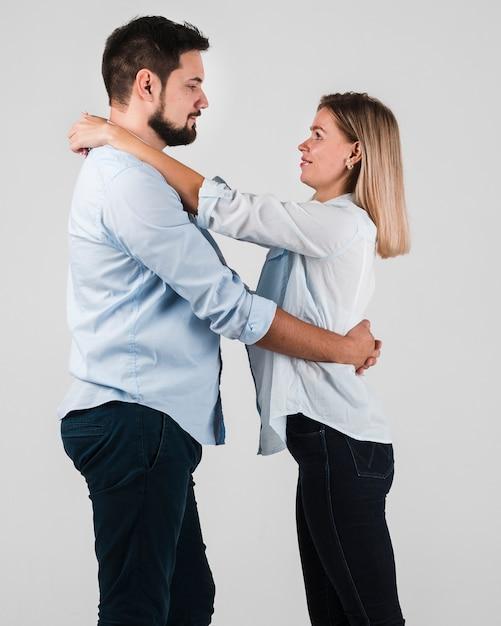 Vista lateral do casal abraçado para dia dos namorados Foto gratuita