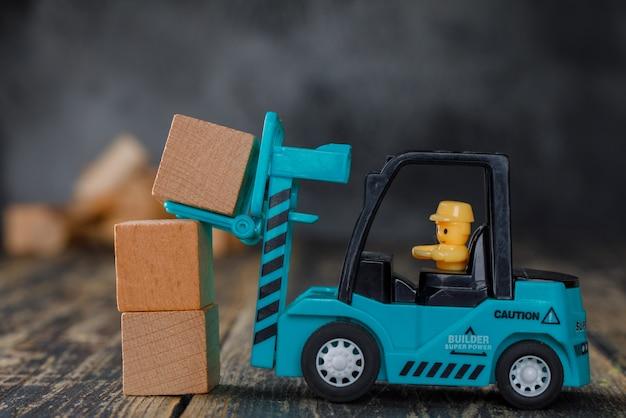 Vista lateral do conceito de planejamento de negócios. empilhadeira empilhando blocos de madeira. Foto gratuita