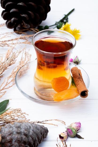 Vista lateral do copo de armudu de chá com damascos secos, pau de canela e botões de rosa secos espalhados em branco Foto gratuita