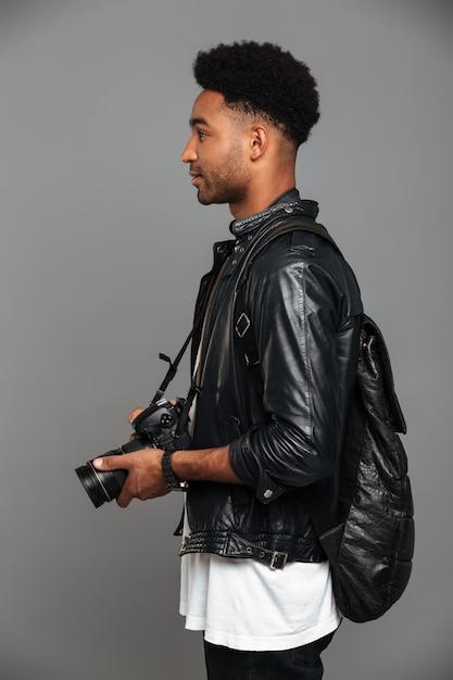 Vista lateral do elegante homem africano elegante com mochila segurando a câmera fotográfica Foto gratuita