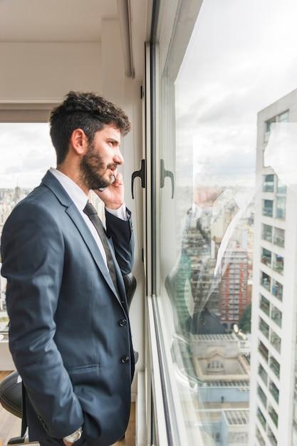 Vista lateral do empresário em pé perto da janela do escritório falando no celular Foto gratuita