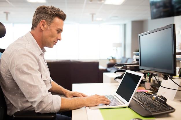 Vista lateral do empresário usando laptop no escritório Foto Premium