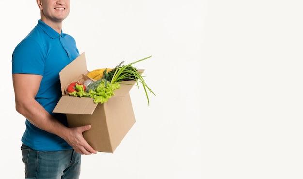 Vista lateral do entregador posando com caixa de supermercado Foto gratuita