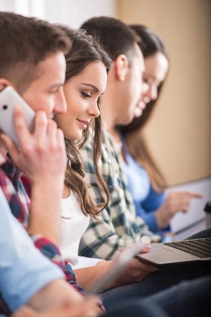 Vista lateral do grupo de estudantes com o laptop. Foto Premium
