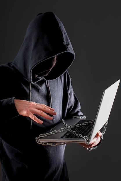 Vista lateral do hacker masculino com laptop protegido por corrente de metal Foto gratuita