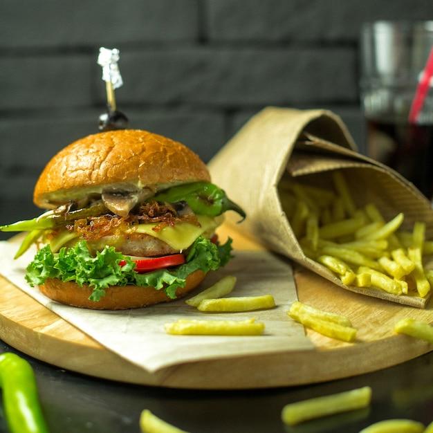 Vista lateral do hambúrguer de frango com queijo derretido tomate e alface, servido com batatas fritas na placa de madeira Foto gratuita