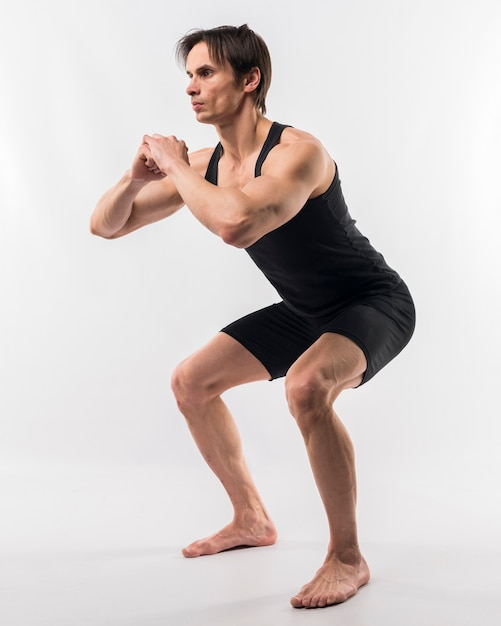 Vista lateral do homem atlético fazendo agachamentos Foto gratuita