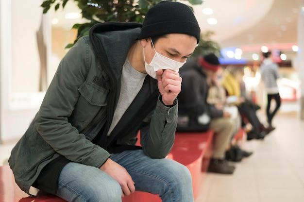 Vista lateral do homem com máscara médica tossindo enquanto no shopping Foto Premium