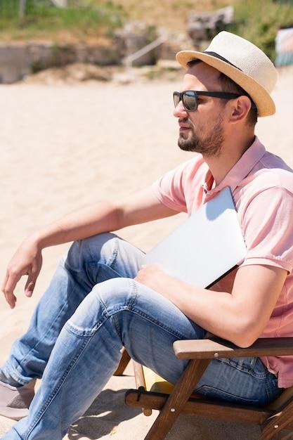 Vista lateral do homem com o laptop na praia Foto gratuita