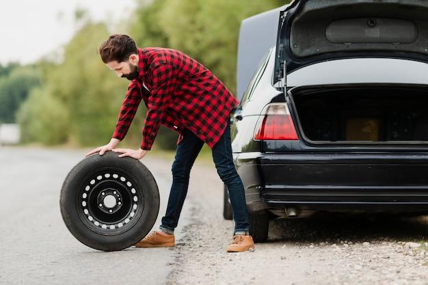 Vista lateral do homem com pneu sobressalente Foto gratuita