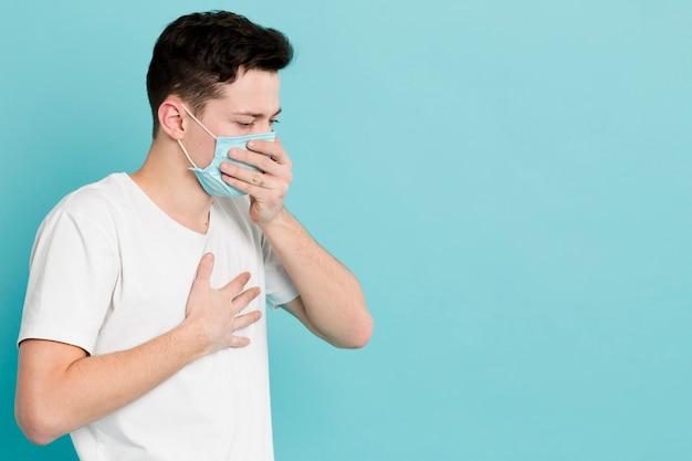 Vista lateral do homem doente, vestindo uma máscara médica Foto gratuita