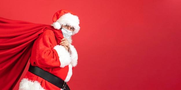 Vista lateral do homem fantasiado de papai noel carregando uma sacola de presente Foto Premium