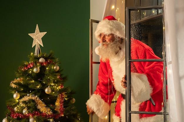 Vista lateral do homem fantasiado de papai noel entrando em casa pela janela Foto gratuita
